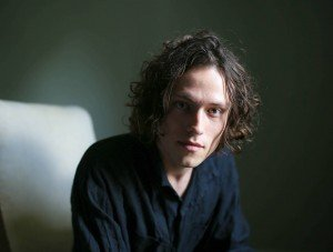 Portrait of Freddie Mercer singer and pianist wearing a black v-neck top with natural light against a teal background and brown curly hair.