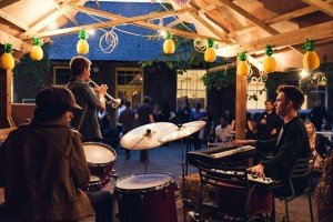 ZEÑEL young Jazz trio playing on an outdoor stage with drums, trumpet and keys.