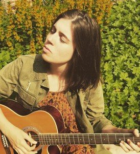 Bryony Dunn against a green leafy background with her acoustic guitar and eyes closed.