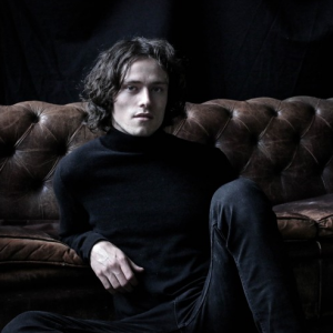 Freddie Mercer with dark leather sofa and black polo neck